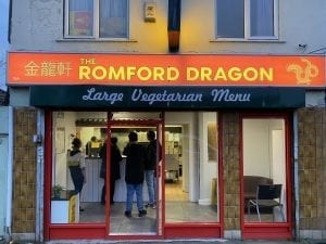 A shopfront with red doors and wide windows. The sign on top in red and gold states the name 'The Romford Dragon' with the address '19A The Parade, Colchester Road, Romford, RM3 0AQ' and finally the phone number '01708 3381818'. Inside the shop looks busy with a cue of people waiting as a woman behind the counter takes orders.