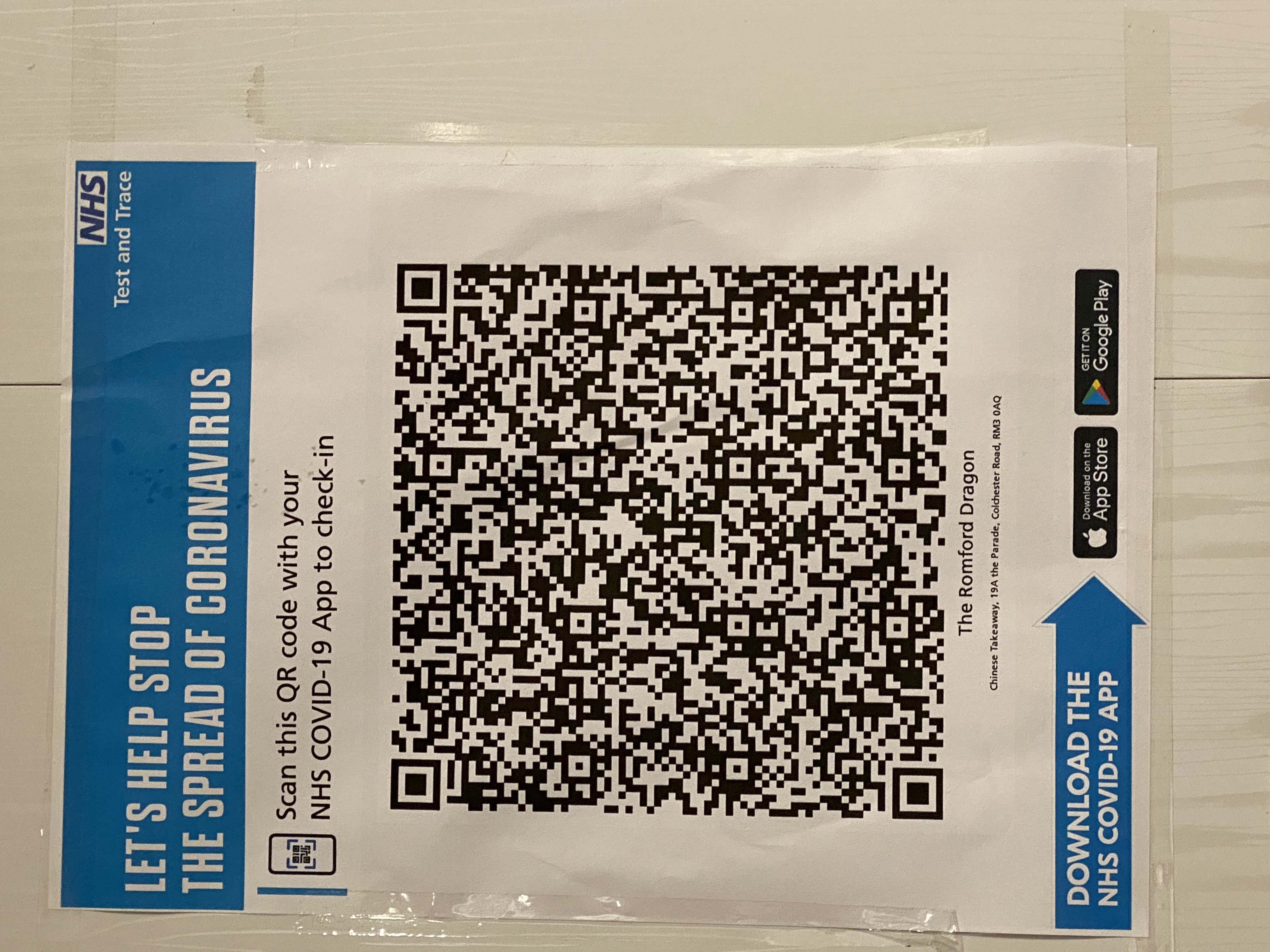 The printout of the NHS sign on a wall. It shows a QR code along with the text: